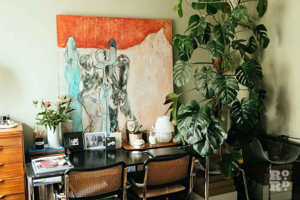 Large canvas and cheese plant in bedroom, stylist Wojtek van Portek in his Bow home.