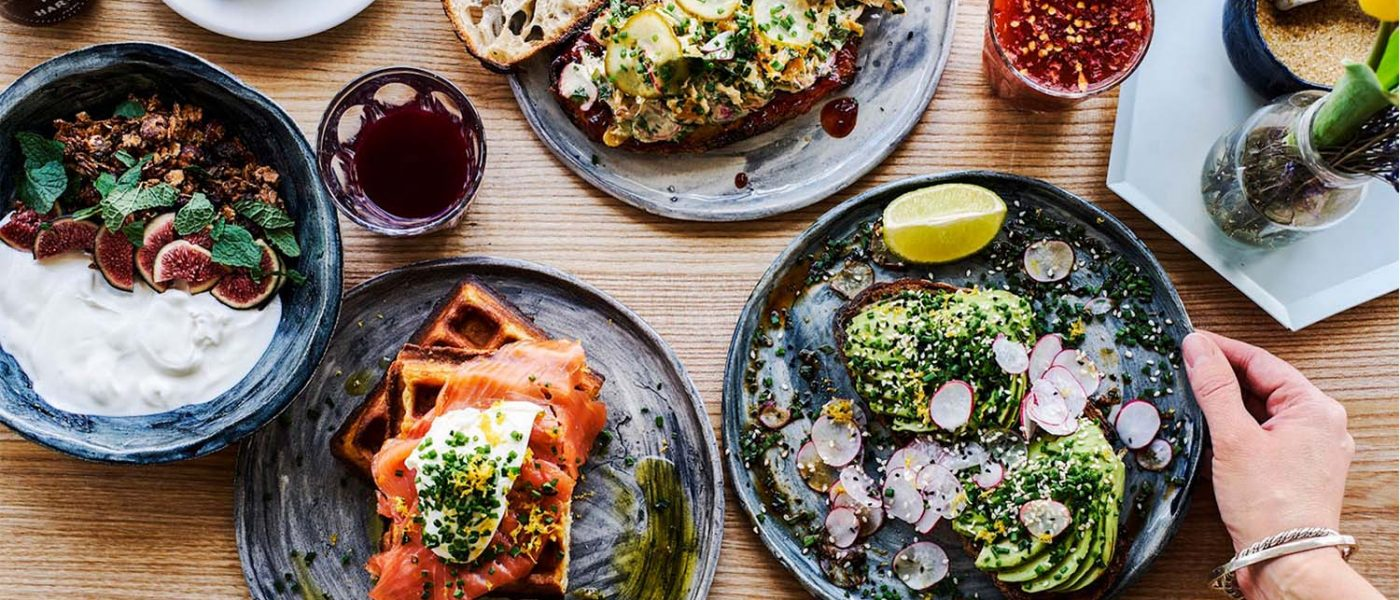 A big brunch spread featuring salmon on toast, avocado, yoghurt and a Bloody Mary.