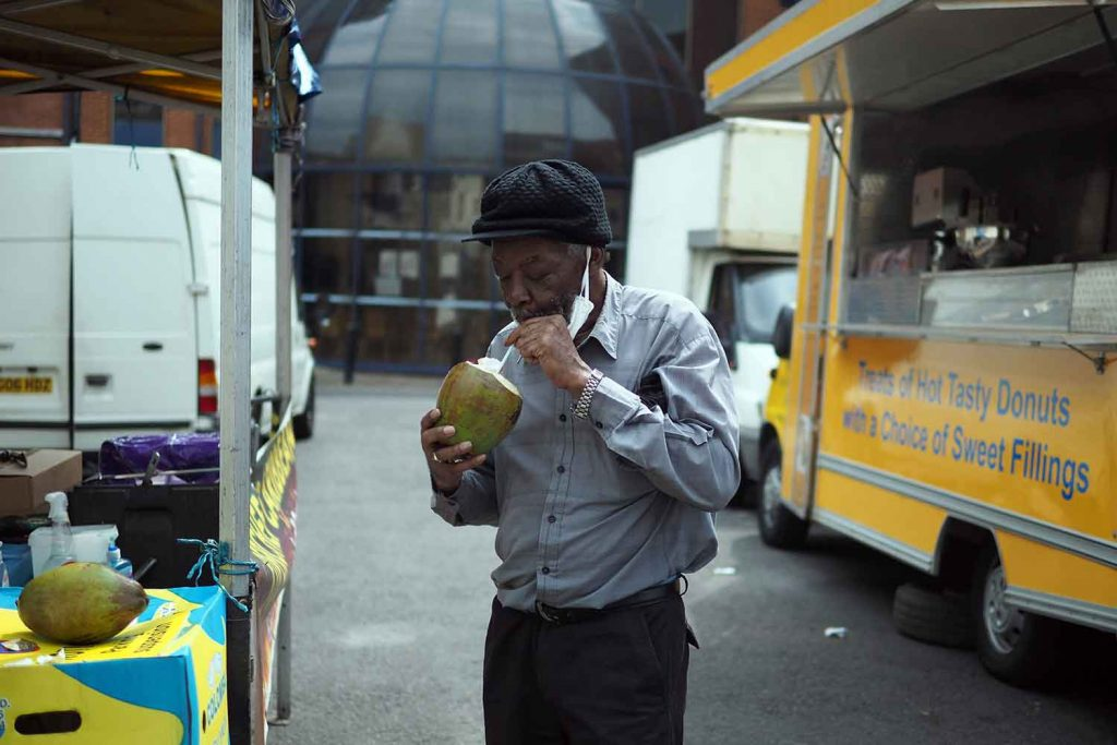 Man eats a green coconut outside a yellow van selling donuts Roman Road Market photoessay from 2020, by photographer Wedgley Snipes.