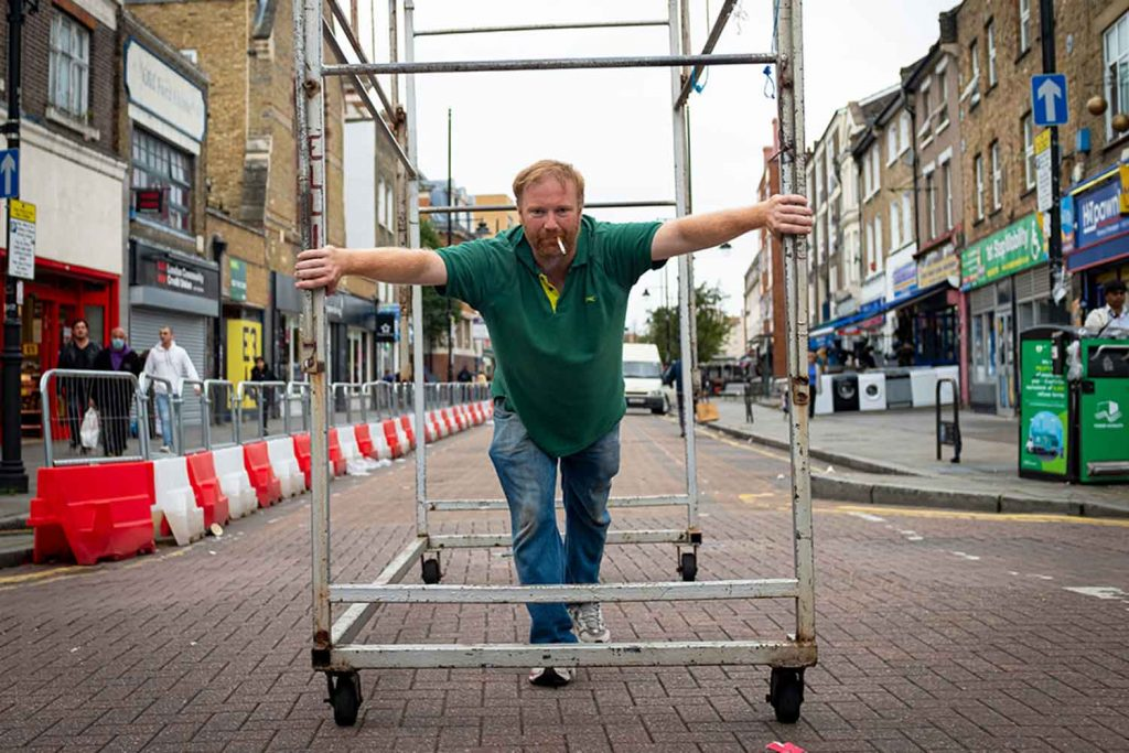 man with a cigarette in his moth pushes the market cages down Roman Road Market photoessay from 2020, by photographer Wedgley Snipes.