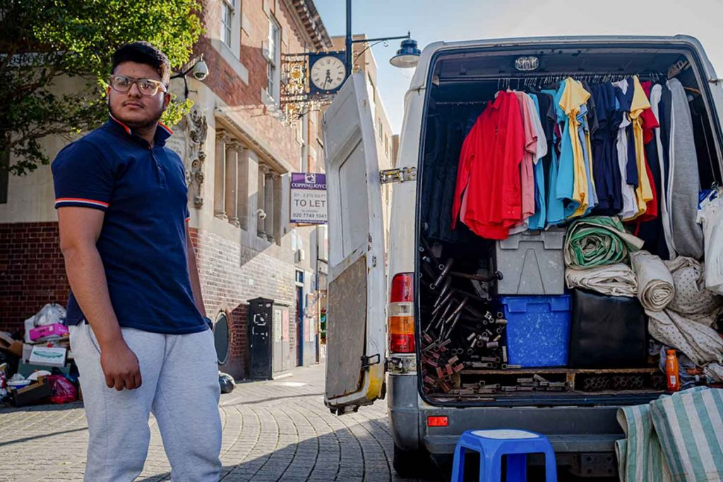 Wa man opens a van containing rows of tops at Roman Road Market photoessay from 2020, by photographer Wedgley Snipes.