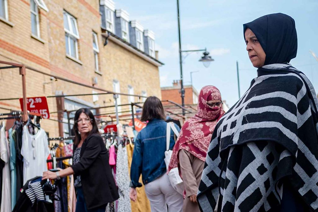 A woman with a hijab watches passers-by at Roman Road Market photoessay from 2020, by photographer Wedgley Snipes.