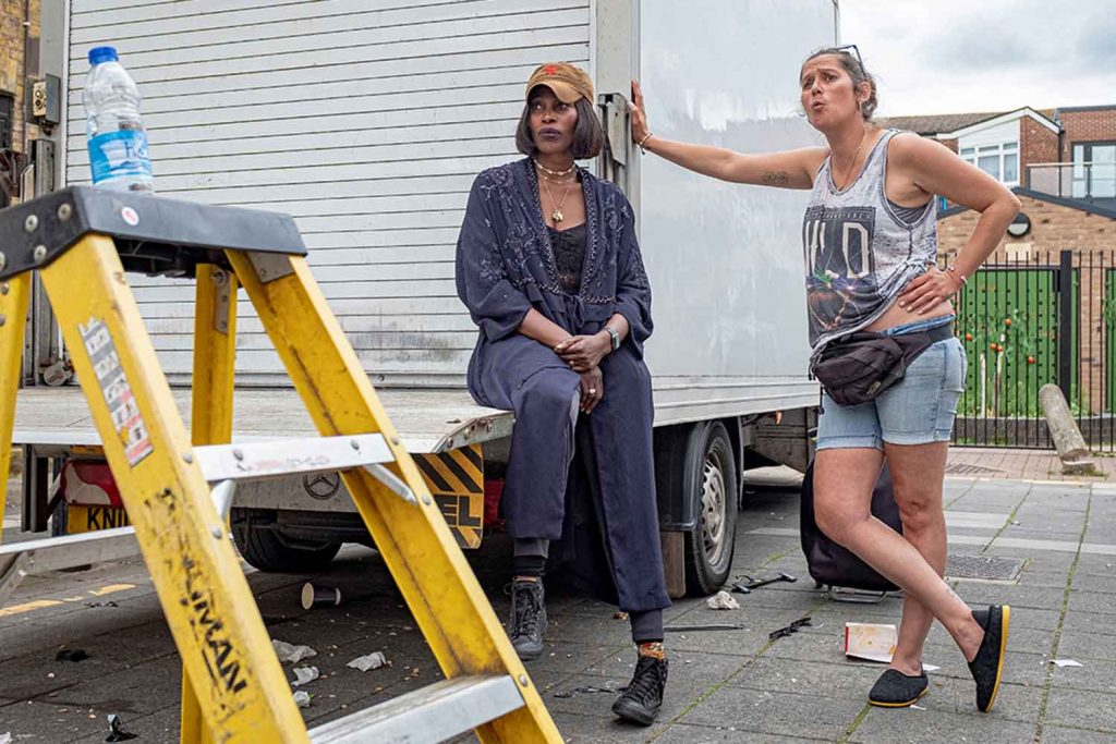 Two women lean against a white truck on Roman Road Market photoessay from 2020, by photographer Wedgley Snipes.