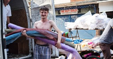 A man with his shirt off holds rolls of fabric at Roman Road Market photoessay from 2020, by photographer Wedgley Snipes.