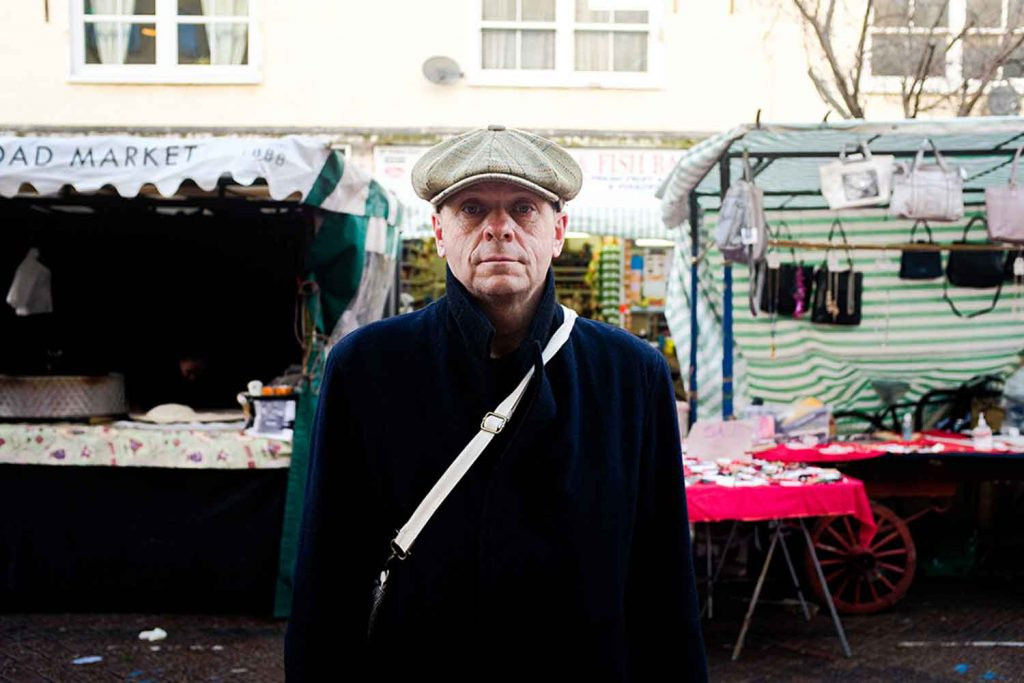 A man wearing a flat cap stands infront of a handbag stall at Roman Road Market photoessay from 2020, by photographer Wedgley Snipes.