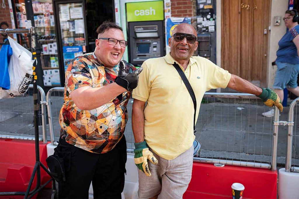 Two men laugh leaning on bollards at Roman Road Market photoessay from 2020, by photographer Wedgley Snipes.