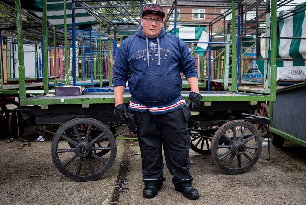 A man stands infant of the market trailers at Roman Road Market photoessay from 2020, by photographer Wedgley Snipes.