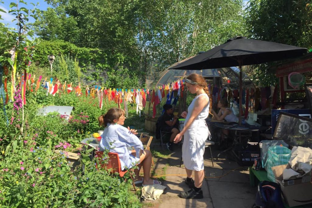 two women stand in the canal club community garden