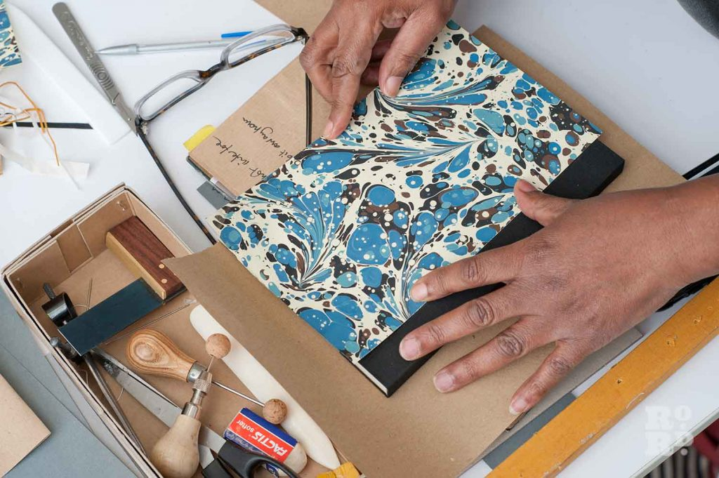 Hands assemble a marble printed notebook at the London Centre for Book Arts