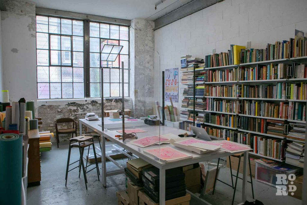 Books line the walls next to newly made prints London Centre Book Arts