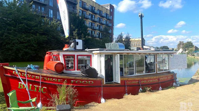 Red fishing boat moored by the canalside, next to a walk path