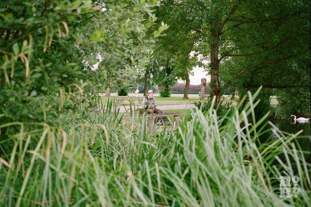Bernie Wighton through the long grass, fishing in Victoria Park, East London.