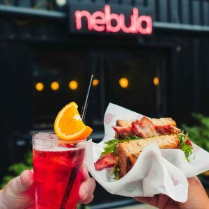 Red cocktail and bacon sandwich held in front of bar called Nebula