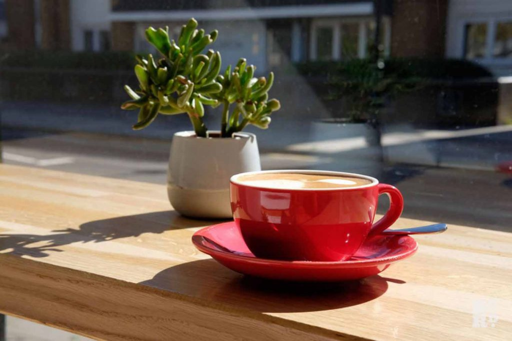 Coffee in a red cup and saucer, Symposium, East London.
