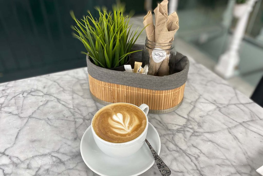 Coffee in white cup, with saucer, on a marble effect table and small plant pot