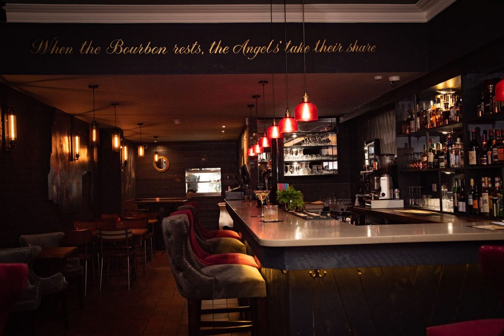 The inside of The Bourbon, with bar stools and the bar, Roman Road, East London